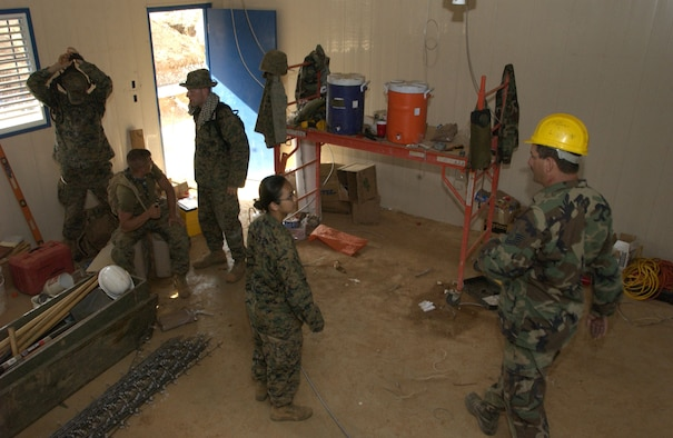 MACARACAS, Panama -- Tech. Sgt. George Lyon (right) instructs Marine Lance Cpl. Leaphy Khim on construction site protocol here.  Both are deployed to Joint Task Force Armadillo, part of New Horizons 2005, a U.S. Southern Command-sponsored readiness training humanitarian exercise.  He is a power production craftsman with the 349th Civil Engineer Squadron at Travis Air Force Base, Calif.  (U.S. Air Force photo by Master Sgt. Lono Kollars)