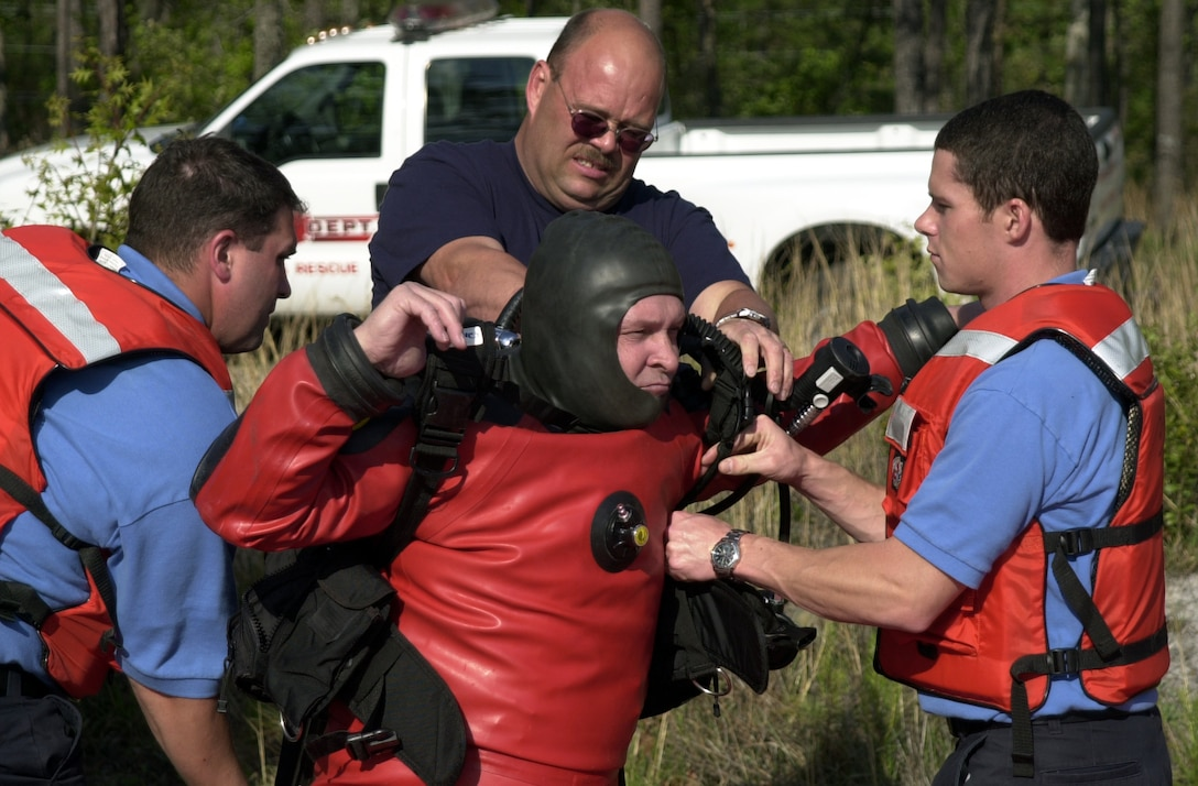 """MARINE CORPS BASE CAMP LEJEUNE, N.C. -Philip Saunders, dive coordinator for the Camp Lejeune Dive Rescue team, gets help from three rescue diver candidates in putting on his dry diving suit April 28.  The dry suit, while more difficult to prepare, allows the diver to complete more varied missions than the traditional wetsuit.  """"I see our dive operations building and expanding from what they are now,"""" said Saunders. """"When our team is filled, I am hoping to begin training for more dangerous work, such as dives with hazardous materials present."""" (Official Marine Corps photo by Lance Cpl. Shane Suzuki)"""