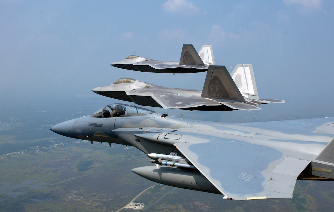 LANGLEY AIR FORCE BASE, Va. -- Two F/A-22 Raptors and a F-15 Eagle fly in formation during a training sortie here.  The 27th Fighter Squadron currently has five permanently assigned Raptors.  (U.S. Air Force photo by Tech. Sgt. Ben Bloker)