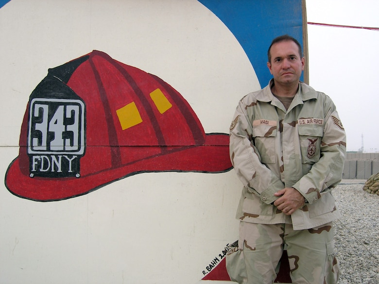 ALI BASE, Iraq -- Staff Sgt. Gregg Magi poses in front of a mural remembering the 343 firefighters who lost their lives at Ground Zero trying to help the victims of Sept. 11, 2001.  Sergeant Magi was promoted to the rank of lieutenant in the Fire Department City of New York during a ceremony via telephone Aug. 16.  He is a firefighter with the 407th Expeditionary Civil Engineer Squadron and is deployed from the New York Air National Guard's 105th Airlift Wing.  (U.S. Air Force photo by Tech. Sgt. Melissa Phillips)
