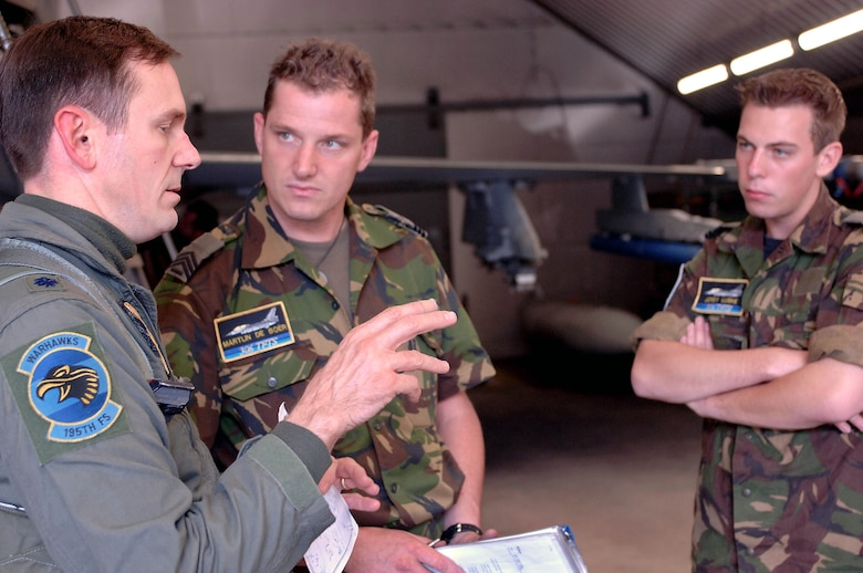 VOLKEL AIR BASE, Netherlands -- Lt. Col. David Stein talks about a sortie with Dutch air force crew chiefs Sgt. Martijn De Boer and Cpl. Jordy Luske.  The colonel is an exchange pilot from the Arizona Air National Guard's 162nd Fighter Wing at Tucson, Ariz.  After a three-year tour with the Dutch air force's 1st Fighter Wing, he will soon return home and pass on what he has learned about the Netherlands's NATO role to his fellow pilots.  (U.S. Air Force photo by Senior Master Sgt. Keith Reed)