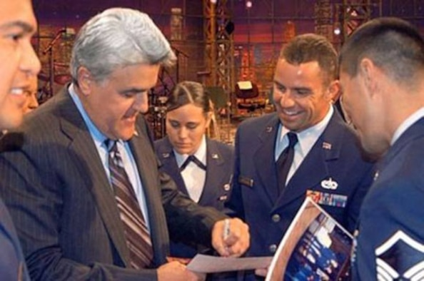"""BURBANK, Calif. (AFMCNS) - Jay Leno, host of """"The Tonight Show,"""" autographs a photo for Master Sgt. Michael Hordichok, 31st Test and Evaluation Squadron program manager, at NBC Studios in Burbank, Calif., on Nov. 22. Mr. Leno invited more than 350 servicemembers, including 55 Airmen from Edwards, to be the audience for the taping of his Thanksgiving Day episode. (Air Force photo)"""