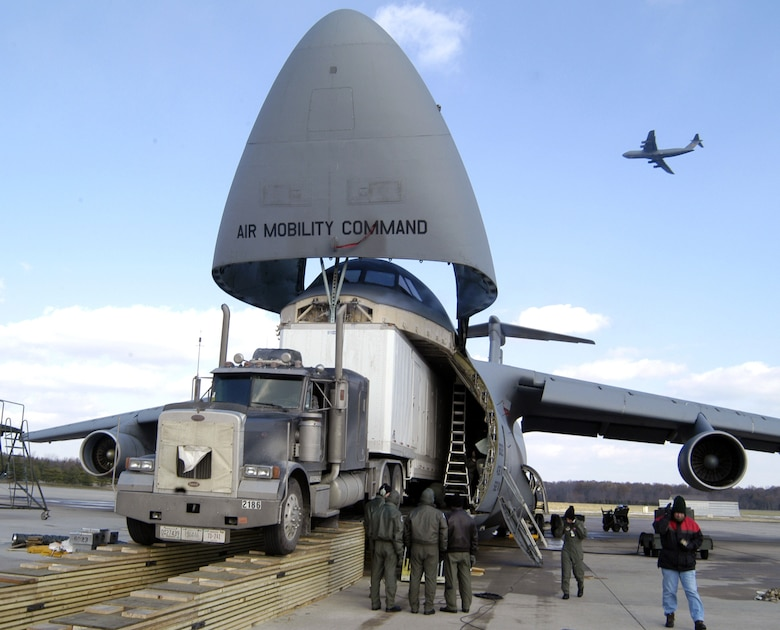 DOVER AIR FORCE BASE, Del. (AFPN) -- Airmen load the Aviation Combined Arms Tactical Trainer onto a C-5 Galaxy with the help of Army contractors. The trainer is an Army helicopter training simulator. Airmen from the 436th Aerial Port Squadron built a ramp specially designed to load the trainer on the transport. Before the ramp's creation, the only way to move the trainer was by ship, which took six to eight weeks to get to Soldiers in the field. (U.S. Air Force photo by Staff Sgt. James Wilkinson)