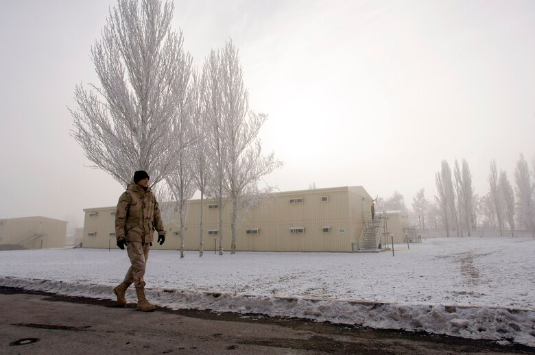MANAS AIR BASE, Kyrgyzstan (AFPN) -- An Airman with the 376th Air Expeditionary Wing walks past the new dormitories here. The base houses nearly 7,000 people who move in and out of the region. (U.S. Air Force photo by Master Sgt. John E. Lasky)