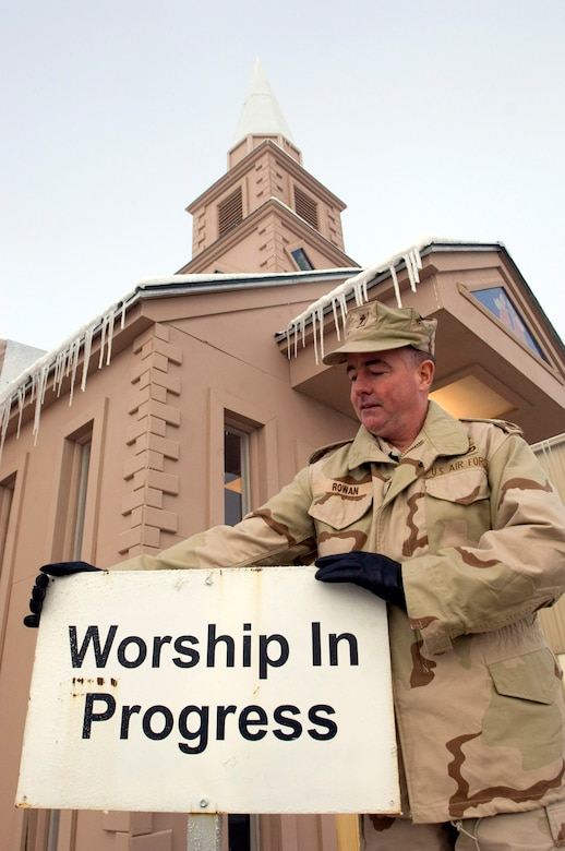 "MANAS AIR BASE, Kyrgyzstan (AFPN) -- Chaplain (Maj.) Mark Rowan places the ""Worship in Progress"" sign outside the chapel here. Volunteers have renovated the chapel and built a steeple. It is the tallest in the region. Major Rowan is the Catholic chaplain for the 376th Air Expeditionary Wing. (U.S. Air Force photo by Master Sgt. John E. Lasky)"
