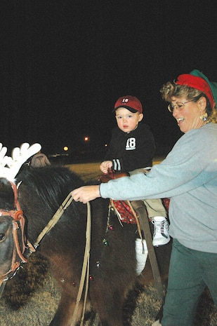 Anthony Lacovara, 2, takes a ride on Colorin under the close supervision of Carrie Tidaback, owner of Party Pony Rides with Colorin, at the Ho, Ho, Ho Down Dec. 16 on the station parade field. The event featured attractions for the whole family, ranging from pony rides and face painting to tractor rides and raffles throughout the night. Free refreshments were provided in the form of cotton candy, popcorn and soda.