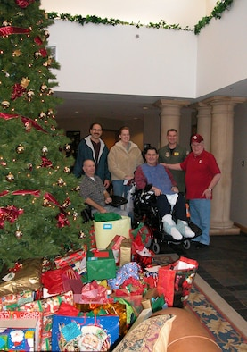 Air Force Reserve 'Angels' (Back row left to right) SMSgt. Bob Gaspar, SSgt. Colleen Rehm and Maj. Jimmy Wolfe pose with residents of the Norman Veterans Center during 2004.  Reservists from the 507th Air Refueling Wing and 513th Air Control Group surpassed last year's 179 gifts to provide 254 gifts for center residents in 2005 year.  A party for the veterans will be held December 22.
