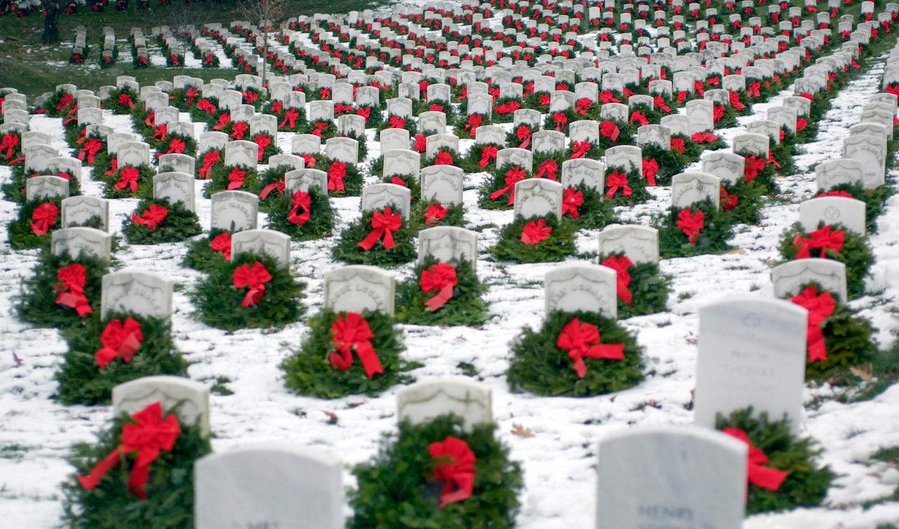 Christmas wreaths adorn headstones in snowy cemetery.