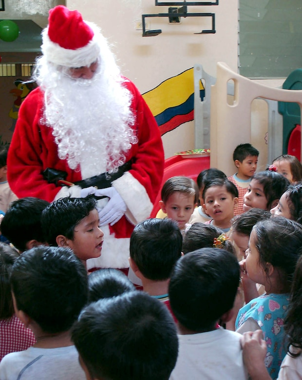 MANTA AIR BASE, Ecuador (AFPN) -- Santa Claus listens to children sing after they received toys at an elementary school. Airmen will be giving 1,800 toys to children at schools, hospitals and other organizations for the holidays. (U.S. Air Force photo)