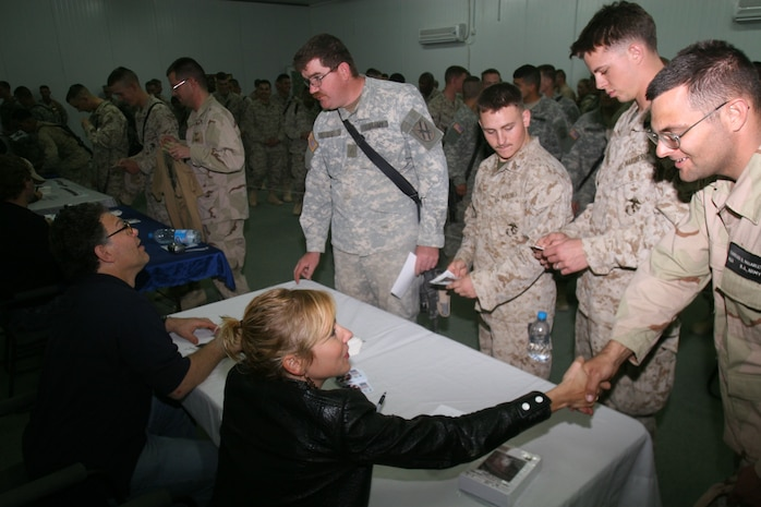 Actress Traylor Howard and comedian Al Franken sign autographs for Marines, Soldiers and Sailors after performing in the United Service Organizations? Hope and Freedom Tour 2005 at Al Asad, Iraq, Dec. 22.