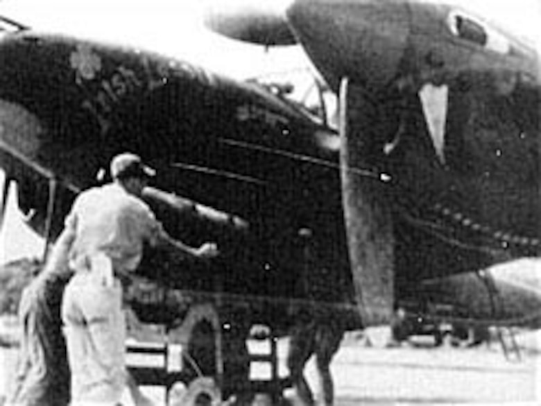 Armorers load a depth bomb on a P-38J Lightning at an airbase in India in January 1945. Such bombs could be fused for either underwater or surface targets. (U.S. Air Force photo)