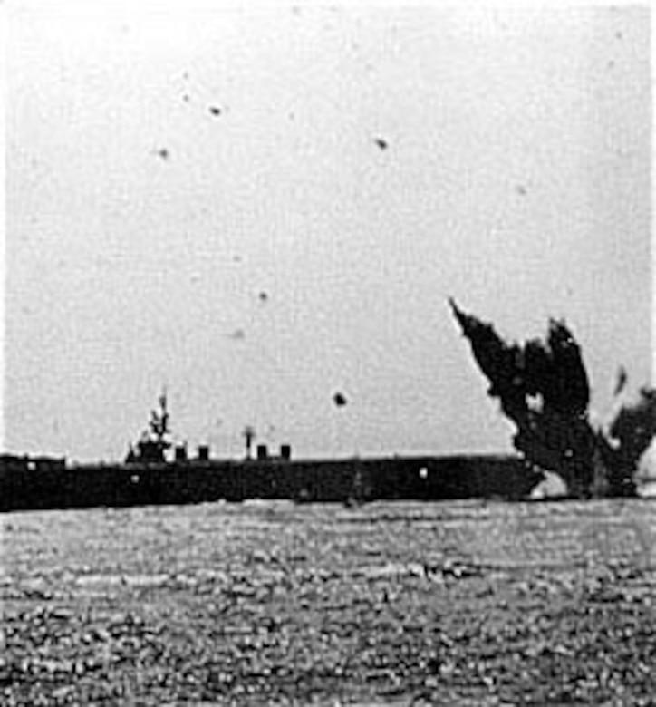 A kamikaze plane crashes just astern of a light carrier beneath a sky filled with antiaircraft bursts. (U.S. Air Force photo)