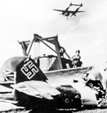 Symbolic of the Nazi defeat, an AAF fighter lands at a former Luftwaffe airfield as an Me-109 is pushed aside. (U.S. Air Force photo)