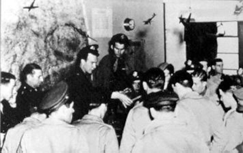 Lt. Col. Stillman briefs the combat crews for an earlier B-26 mission flown May 14, 1943. They are studying a model of the target, the power plant at Ijmuiden, Holland. (U.S. Air Force photo)