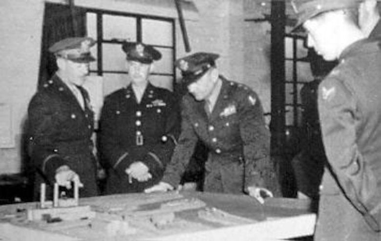 "Maj. Gen. Francis S. Brady, Commanding Officer of the B-26 unit that lost all 10 planes on the May 17, 1943, mission, ""explains"" to Maj. Gen. Ira C. Eaker why none returned to England. They are looking at the same model of the target as the crews in the next photograph. (U.S. Air Force photo)"