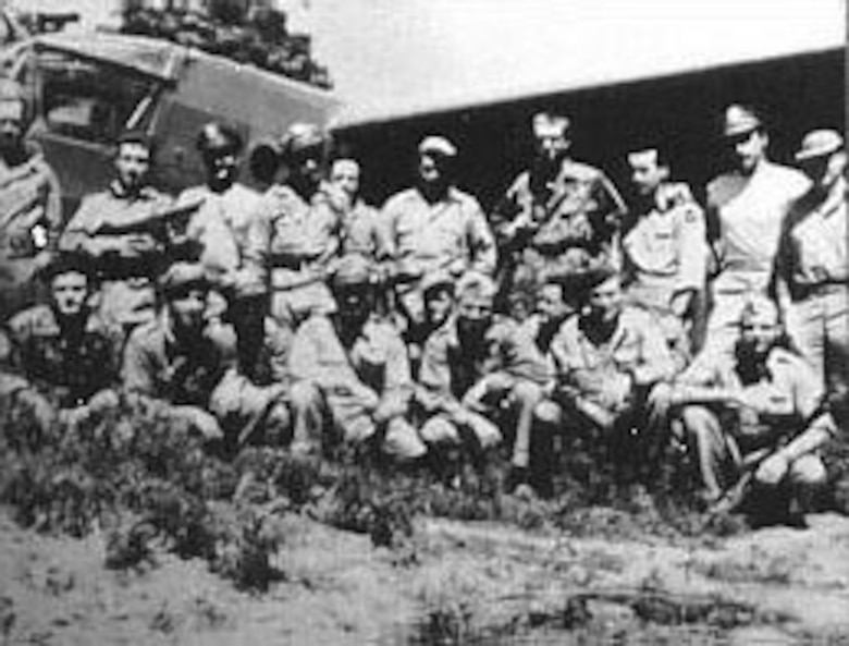 Members of the 1st Air Commando Group in India just before taking off on the glider invasion of Burma. Jackie Coogan is kneeling at right with gun on left arm. In rear is a CG-4A glider. (U.S. Air Force photo)