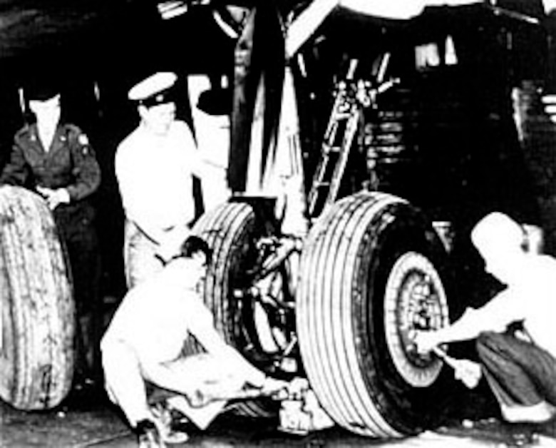 U.S. Navy support personnel from VR-6, assisted by an Air Force enlisted man, change a tire on a Navy R-5D (C-54). (U.S. Air Force photo)