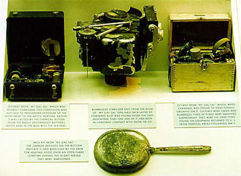 "Four items were recovered from ""My Gal Sal"" when it was re-discovered in October 1964. Top left of photo: Sextant from ""My Gal Sal"" that was severely corroded. This corrosion was not due to prolonged exposure of the instrument to the Arctic weather; rather, it was caused by the chemical action from the badly decomposed batteries that were in the box with the sextant. Top center: Bombsight stabilizer unit from the nose of ""My Gal Sal."" One half inch layer of powdered rust was found inside the unit, indicating that one side of it had been in constant contact with snow or ice. Top right: Octant from ""My Gal Sal,"" which when examined, was found to have fungus growths on it. Cultures were taken and numerous types of fungi were identified. Surprisingly, they were the same types found on equipment returned to the United States from tropical areas following World War II. Bottom: Mess kit from ""My Gal Sal."" The carbon deposits on the bottom indicate it had been used by the crew for heating food over an open flame sometime during the 10-day period they were marooned. (U.S. Air Force photo)"