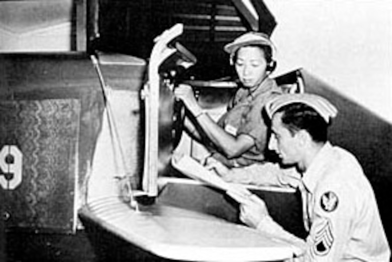 Hazel Ying Lee reviews her performance after a session in a Link trainer. (U.S. Air Force photo)