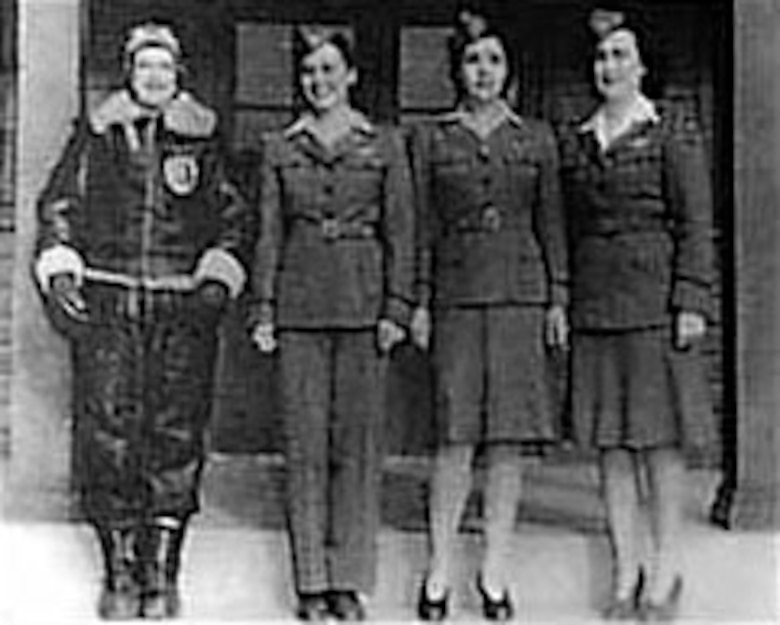 WAFS mdoel various uniforms. From left are Delphine Bohn in two piece winter flying suit; Evelyn Sharp wearing flying and traveling outfit of tan working shirt, gray jacket and trousers; Bernice Batton in same outfit but with dress skirt; and Barbara Erickson in white shirt with gray jacket and gray skirt worn for more formal occasions. (U.S. Air Force photo)
