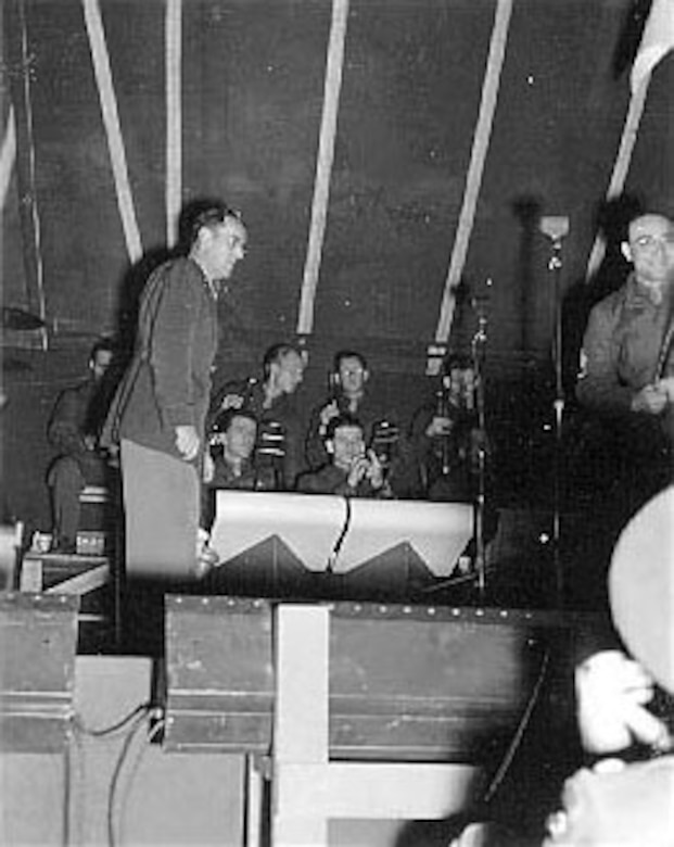 A soldier in the audience takes a photograph of Maj. Glenn Miller as band leader. (U.S. Air Force photo)