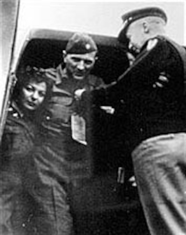 """Lt. Col. Michael """"Mike"""" C. Murphy (center), a pre-World War II stunt pilot who later directed the AAF glider pilot training program. He developed new tow techniques, assisted in the planning for the D-Day invasion of France and led the gliders into Normandy. Here, while preparing for medical evacuation to the United States, he received the Purple Heart for injuries suffered in the crash of the glider during the Normandy Invasion. (U.S. Air Force photo)"""