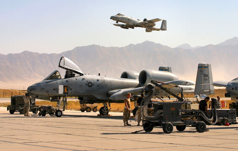 BAGRAM AIR BASE, Afghanistan (AFPN) -- An A-10 Thunderbolt II takes off on a combat mission as A-10 crew chiefs, weapons loaders and an avionics specialist ready others for another mission. Since Sept. 15, A-10s here have flown more than 1,700 combat sorties, totaling more than 6,000 combat hours in support of Operation Enduring Freedom. The A-10 was the first Air Force aircraft specially designed for close air support of ground forces. (U.S. Air Force photo by Chief Master Sgt. David L. Stuppy)