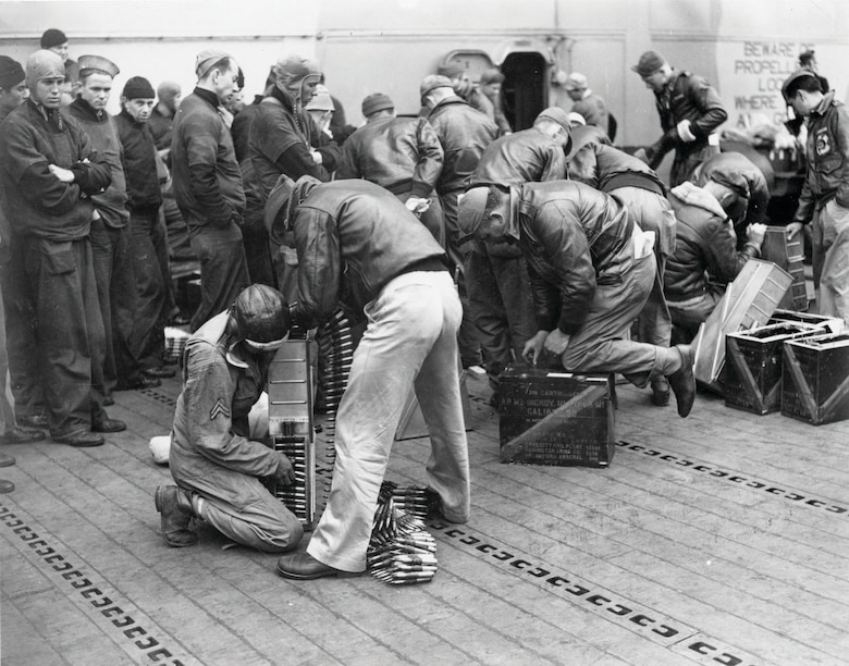 USAAF personnel load .50-cal. ammunition into ammo trays prior to takeoff from the Hornet as Navy personnel watch. (U.S. Air Force photo)