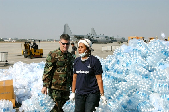 BANGKOK, Thailand -- An Airman here teams up with a Thai volunteer Jan. 1 to organize bottles of drinking water at the international airport.  He and 100 others from the 353rd Special Operations Group are flying supplies to the tsunami-hit areas of southern Thailand.  The 353rd SOG is assigned to Kadena Air Base, Japan.  (U.S. Air Force photo by Master Sgt. Michael Farris)