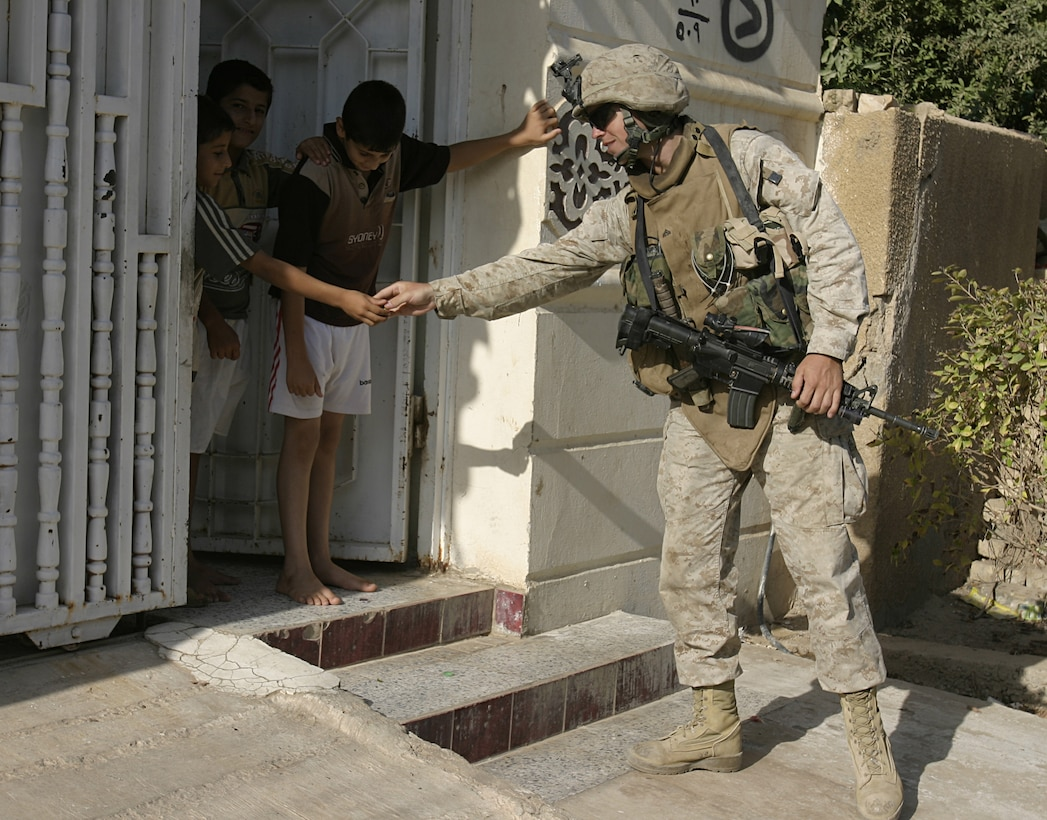 FALLUJAH, Iraq - Corporal Justin Henshaw, an infantryman with 4th Combined Anti-Armor Team, Weapons Company, 1st Battalion, 6th Marine Regiment, hands candy to local children during a recent patrol here.  The 25-year-old St. Simons Island, Ga. native traded a promising career in acting and personal training to fight the Global War on Terror overseas, where he claims to enjoy helping the Iraqi people rebuild their nation.