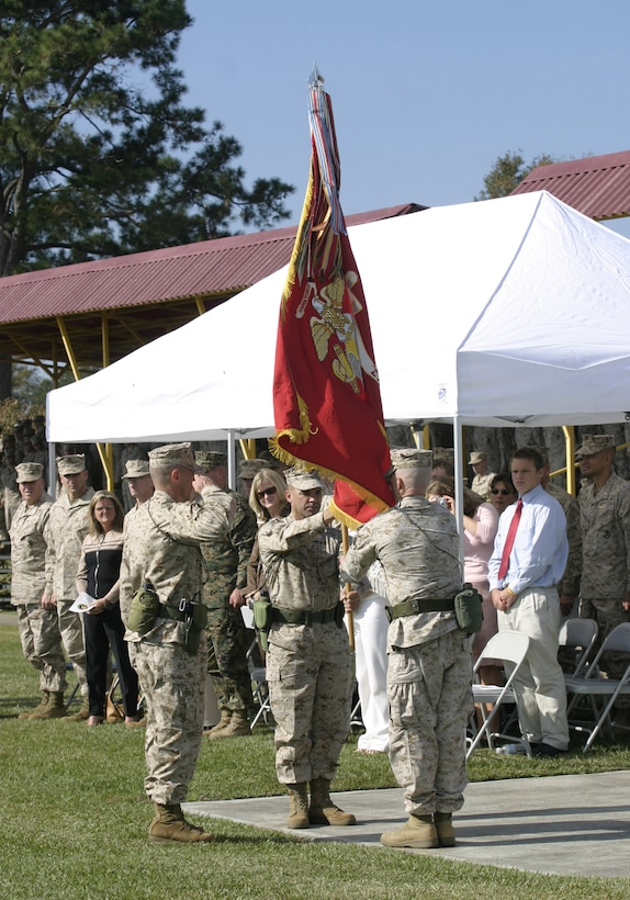 """MARINE CORPS BASE CAMP LEJEUNE, N.C. - Lieutenant Colonel Robert G. Petit, left, hands the 2nd Battalion, 8th Marine Regiment colors to Lt. Col. Kenneth M. DeTreux to symbolize the transfer of authority during a change of command ceremony here Nov. 4.  DeTreux, a native of Philadelphia, assumed command of """"America's Battalion"""" to prepare his Marines for a deployment to Iraq in 2006."""