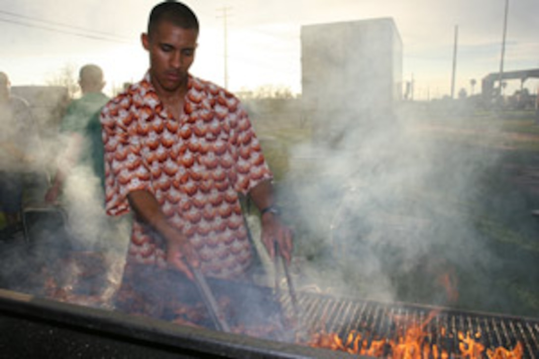 Lance Cpl. Jimmy D. Friesenhahn, a food service specialist with Heaquarters and Service Company, 3rd Battalion, 7th Marine Regiment, fights flames and thick smoke as he prepares more than 1,000 servings of pork ribs during 3/7?s Family Fun Night Aug. 4 at Victory Field.  More than 2,500 people attended the event.