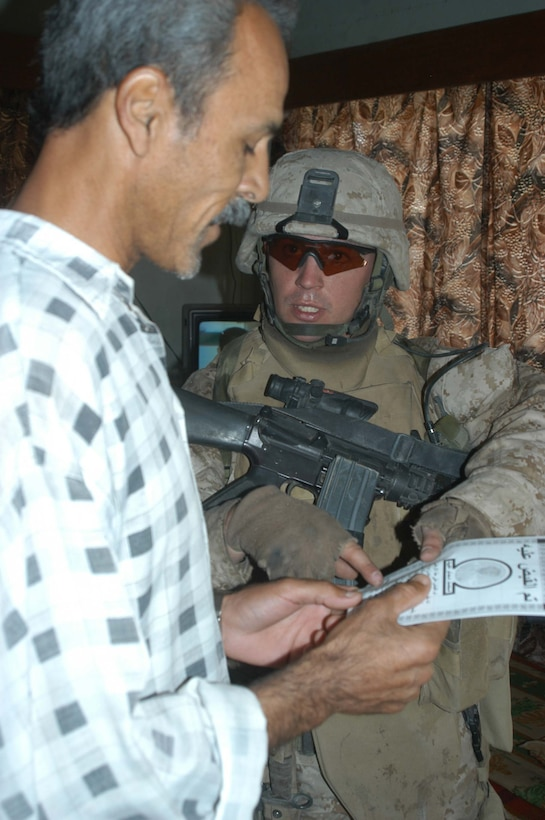 AR RAMADI, Iraq (May 27, 2005) - During a mission in the city here, Staff Sgt. James M. Hussey, the platoon sergeant for 4th Platoon, Company A, 1st Battalion, 5th Marine Regiment, hands an Iraqi man a pro-coalition forces flier and points to a number he can call to report insurgent activity to coalition forces. The 28-year-old from Poughkeepsie, N.Y., led his fellow 4th Platoon warriors on a four-hour aggressive-foot-patrol through several neighborhoods and the city's marketplace. The Marines searched 12 houses and talked to numerous locals during the mission, which was conducted in an attempt to stifle insurgent activity and inform citizens why Marines and coalition forces are occupying Ramadi. The Marines handed out pro-coalition forces and pro-Iraqi government fliers, which had a number to call coalition forces to report insurgent activity. Photo by: Cpl. Tom Sloan