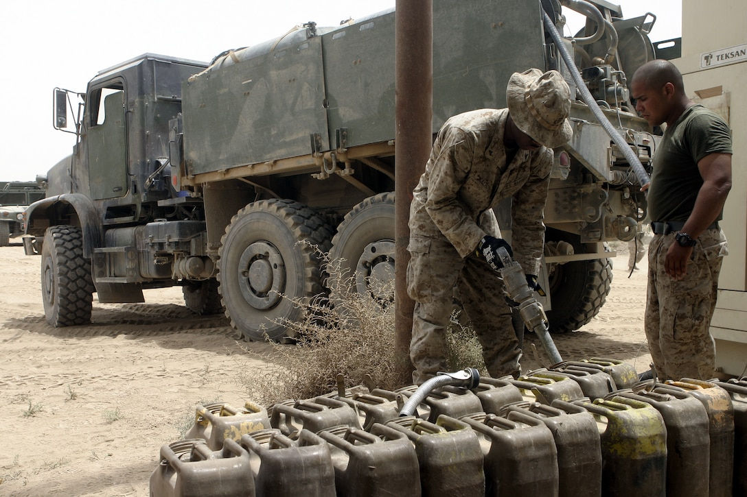 SAQLAWIYAH, Iraq - Lance Cpl. Romaine H. Mullings, a motor transport operator with 1st Battalion, 6th Marine Regiment, refills an infantry base's diesel fuel jugs here July 18.  The 21-year-old West Palm Beach, Fla. native is one of many Marines who perform daily logistics runs to the infantrymen's operational headquarters to re-supply them with water, fuel, and food rations, along with replacing broken appliances and vehicles.