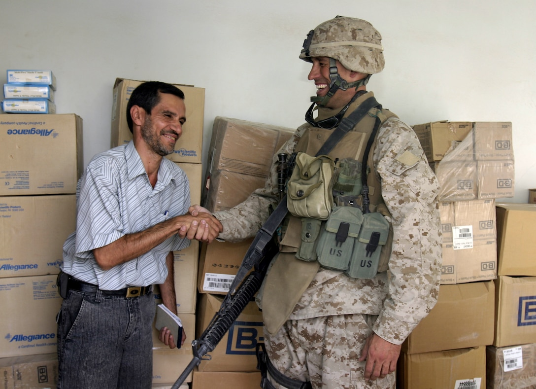 SAQLAWIYAH, Iraq - Major Chris E. Phelps, Team 3, Detachment 2, 5th Civil Affairs Group team leader and Shawnee, Kan. native, shakes hands with Dr. Ayad al-Hadithy, a doctor at the Saqlawiyah medical clinic, Sept. 7 after the CAG Marines dropped off boxes of supplies for the clinic.  The Marines distributed more than $4,000 worth of medical supplies that were donated by the Kansas-based nongovernmental organization Heart to Heart International to the clinic here.  Team 3 Marines have operated in and around this area since April to help restore the city's government, police force and infrastructure.