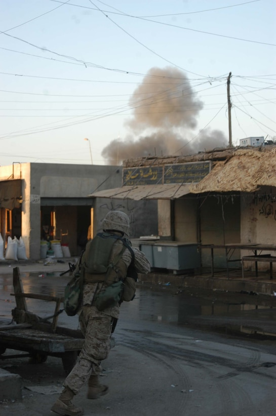 AR RAMADI, Iraq (April 8, 2005) - Lance Cpl. Micheal D. O'Rielly, a 22-year-old rifleman with 1st Squad, 4th Platoon, Company A, 1st Battalion, 5th Marine Regiment, looks to his left down a street in the marketplace here for someone who might have just detonated the improvised explosive device a block away. The deafening blast sent a mushroom cloud of smoke into the air. Another IED went off in the area minutes later. No one was hurt. Marines with 4th Platoon, Company A, 1st Battalion, 5th Marines patrolled the marketplace in an effort to familiarize themselves with their area of operations and determine how the local Iraqis feel about their presence in the area. The Marines also handed out positive and anti-insurgent propaganda to the Iraqis and searched for insurgents and things out of the ordinary during the two-hour operation. Photo by Cpl. Tom Sloan