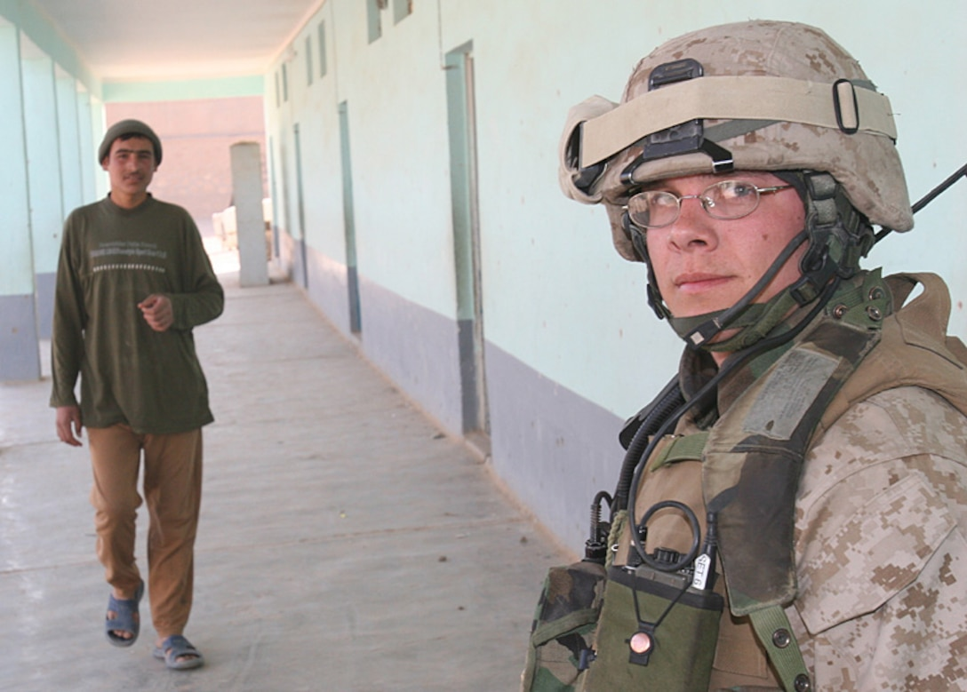 Cpl. Jason L. Johnson, 23, radio field operator, 6th Civil Affairs Group, stands watch while the rest of his patrol reviews a Husbayah, Iraq school. Johnson deployed with 6th CAG to Iraq August 2005 in support of Operation Iraqi Freedom.