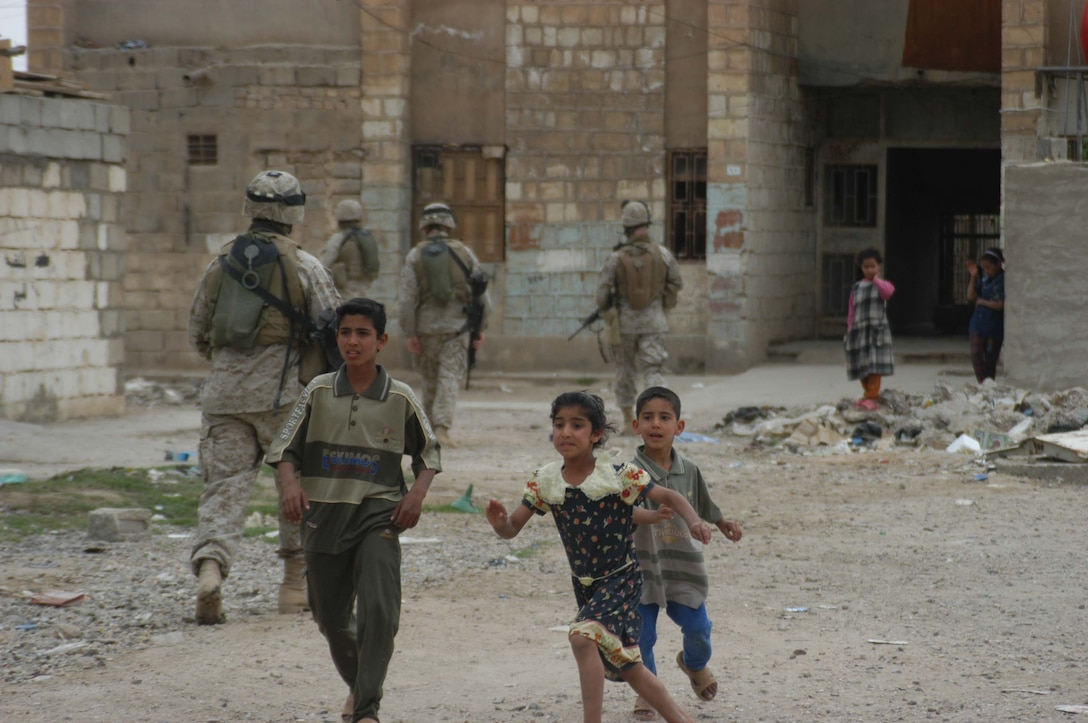 """AR RAMADI, Iraq (April 9, 2005) - Iraqi children run out from their homes in a neighborhood here to greet Marines with 2nd Squad, 2nd Platoon, Company C, 1st Battalion, 5th Marine Regiment, conducting a patrol. The infantry battalion has labeled the neighborhood the city's """"Ghetto."""" Patrols here often include interaction with Iraqi children. Photo by Cpl. Tom Sloan"""