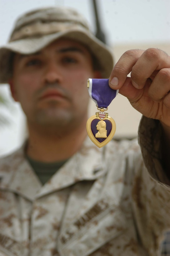 CAMP HURRICANE POINT Ar Ramadi, Iraq (Aug. 9, 2005) - Lance Cpl. Jose O. Martinez, a machine gunner with 4th Platoon, Company W, 1st Battalion, 5th Marine Regiment, narrowly escaped death June 11. The 22-year-old from El Paso, Texas was hit in the face, neck and the back of his head by shrapnel from an improvised explosive device while conducting a night mission with his Marine comrades. For his wounds, Martinez was awarded a Purple Heart during a ceremony here Aug. 2. Martinez is in Iraq a second time with 1st Battalion, 5th Marines in support of Operation Iraqi Freedom. He made it through the fighting in Fallujah unscathed. Photo by: Cpl. Tom Sloan
