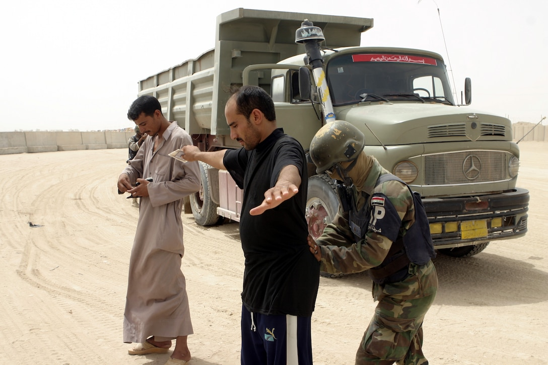 """FALLUJAH, Iraq - An Iraqi policeman pats down residents aboard Fallujah's Entry Control Point-One """"Alpha"""" Aug. 10.  Marines with 1st Battalion, 6th Marine Regiment oversee Iraqi policemen with the Public Order Brigade as they search the thousands of automobiles and local citizens entering the city every day for weapons and contraband."""
