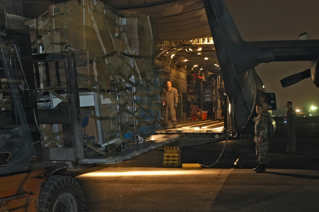 MEDAN, Indonesia -- A loadmaster guides a forklift into position here during a load of humanitarian supplies.  The aircraft made two deliveries into the tsunami-battered region of Banda Aceh on Jan. 8.  Another MC-130H Combat Talon II crew from the 353rd Special Operations group made two additional deliveries.  (U.S. Air Force photo by Master Sgt. Michael Farris)