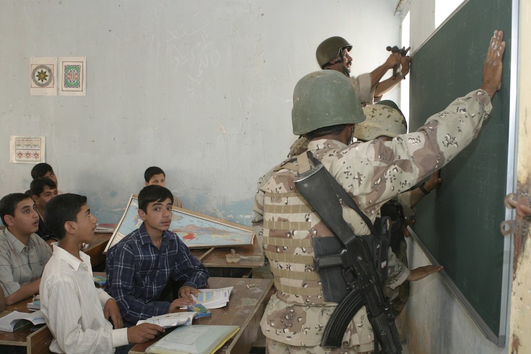 FALLUJAH, Iraq - Iraqi soldiers from the Iraqi Security Forces' 2nd Brigade visit a local school May 12 to hang up new blackboards and speak with the faculty.  The ISF personnel are currently working with Marines from 1st Battalion, 6th Marine Regiment to conduct 'Operation Blackboard,' a joint civil-military mission during which Iraqi soldiers re-supply Fallujah's schools and continue winning the citizens' trust.