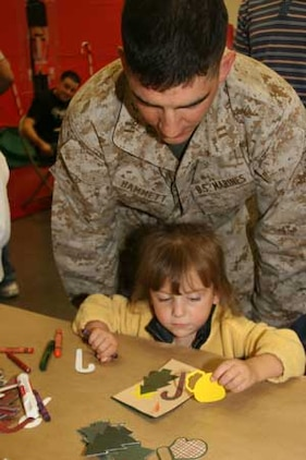 Capt. Eddie Hammett, 1st Tank Battalion, helps his 3-year-old daughter, Lauren, make a Christmas card at the battalion?s Christmas party Dec. 13 at the Community Center. More than 400 Marines with their families attended the event, which had a table full of crafting supplies to create Christmas cards and paper wreathes for the children, among other activities. There was also a Christmas dinner with 12 turkeys and hams along with a variety of side dishes from the base?s food services.