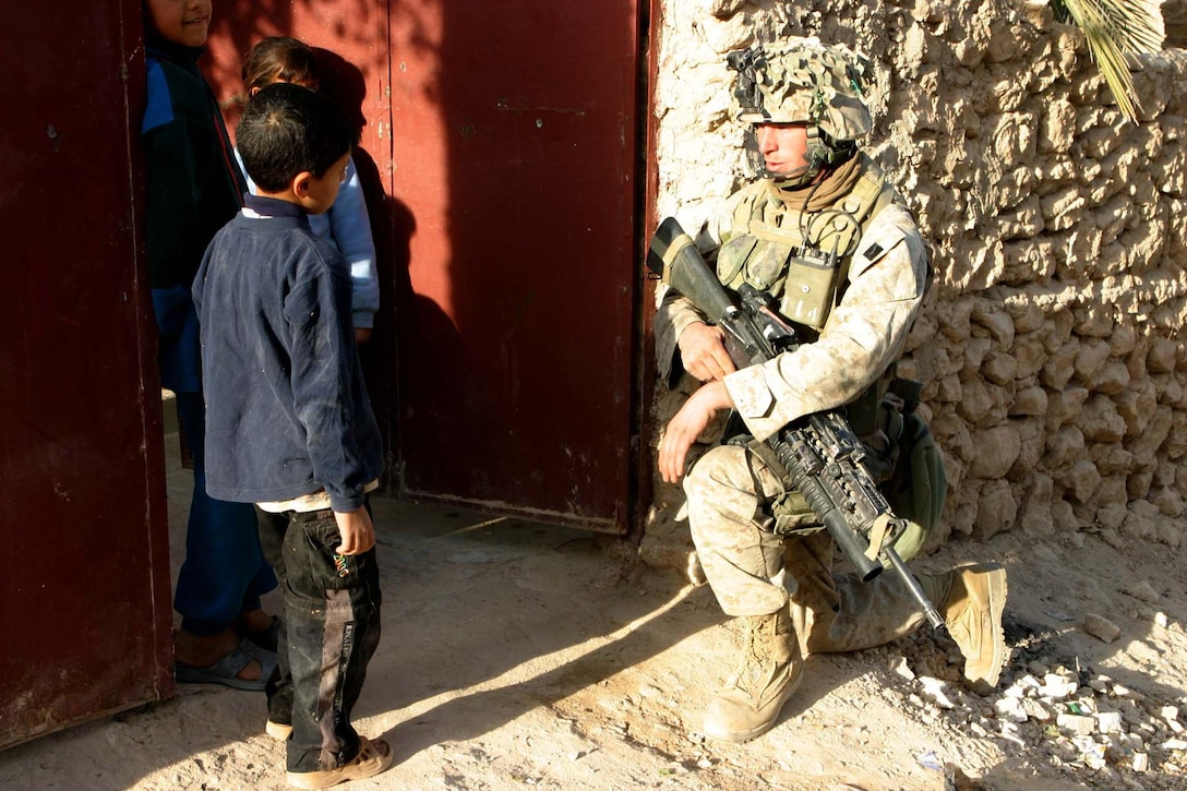 HAQLANIYAH, Iraq (Nov. 27, 2005)  - Woodland, Calif. native, Lance Cpl. Chris P. Stabler, talks with children on a security patrol here Nov. 27. Stabler, a team leader with India Company, 3rd Battalion, 1st Marine Regiment, performs patrols in the city to make sure it is safe for the citizens to have normal lives and to be free of terrorism in the region. (Official Marine Corps photo by Cpl. Adam C. Schnell)