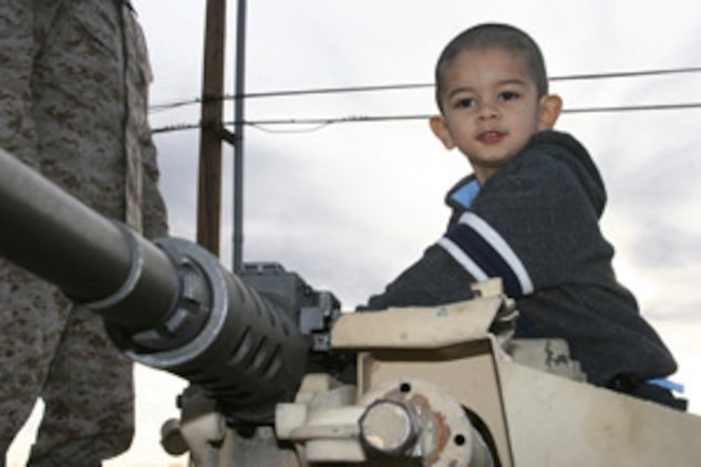Samuel Calderon, 2, sits atop an M1A1 Abrams Main Battle Tank that was part of a static display of vehicles for the Headquarters Company, 7th Marine Regiment, family day Dec. 15 at Victory Field.