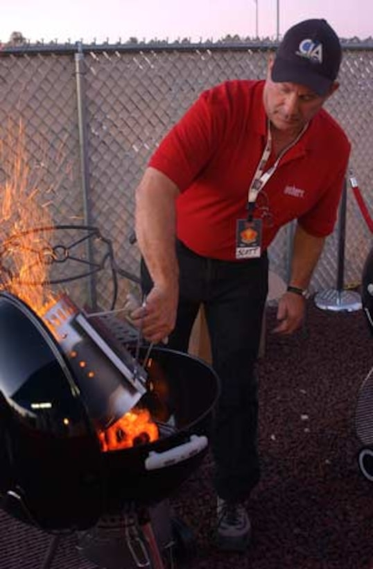 Scott Mintz of Weber Grills dumps charcoal into a grill prior to competitors beginning for the Command of the Grill cooking competition Nov. 16 at the Hashmarks Staff Noncommissioned Officer?s Club.