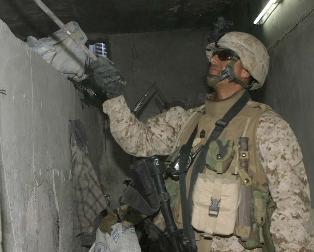 FALLUJAH, Iraq - 1st Sgt. Ernest K. Hoopii, Company C's, 1st Battalion, 6th Marine Regiment first sergeant, uses a stick to probe the walls of the Farwat bakery here April 17 to search for hidden weapons.  Iraqi Security Forces and Company C personnel conducted a raid on the bakery, detained nine suspected insurgent supporters, and confiscated a pistol and numerous forms of anti-Coalition forces propaganda.