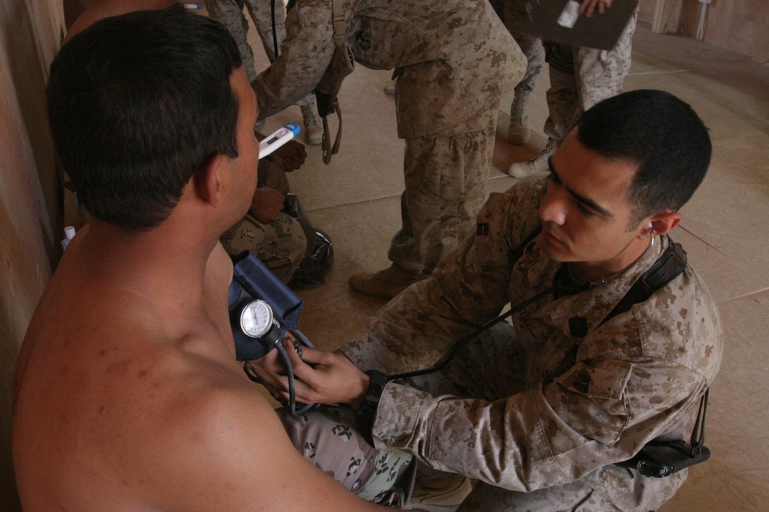 CAMP AL QA'IM, Iraq (July 18, 2005)- Hospital Corpsman 3rd Class (FMF) Roman Cadena, Jr., a corpsman with 3rd Battalion, 2nd Marine Regiment, Regimental Combat Team-2 from Weslaco, Texas, checks an Iraqi soldiers blood pressure during a medical screening here. (Official U.S. Marine Corps photo by Lance Cpl. Lucian Friel (RELEASED)