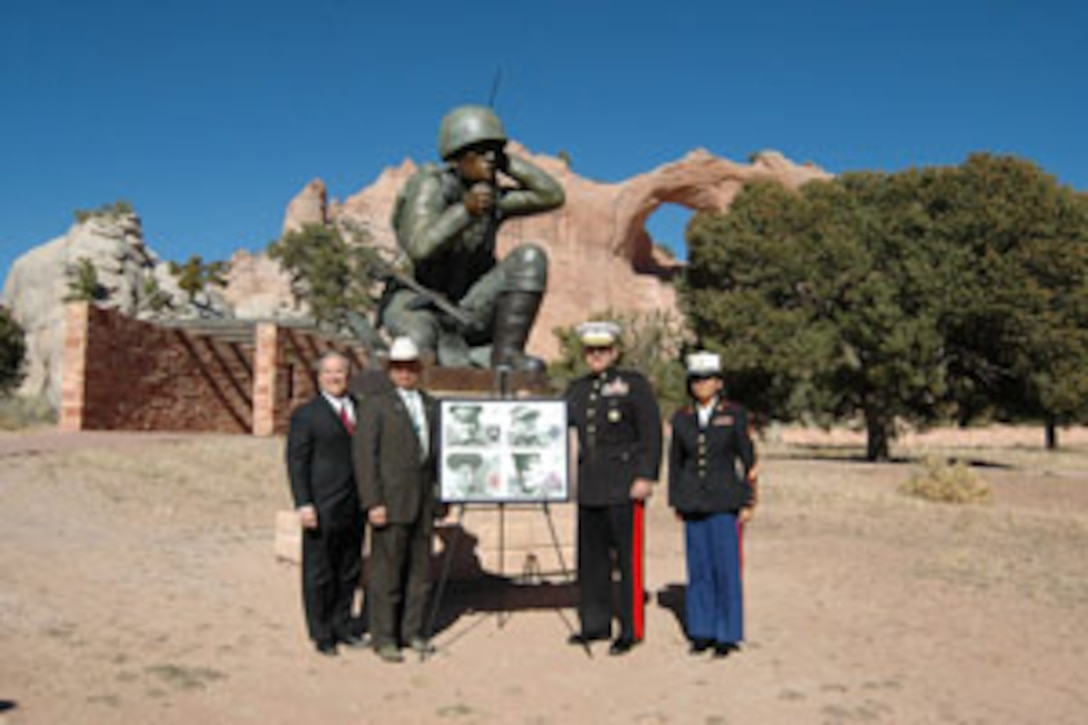 George Lopez, United States Postal Service Southwest area vice-president of operations, Frank Dayish Jr., Navaho Nation vice president, Brig. Gen. Douglas M. Stone, Combat Center deputy commanding general, and Gunnery Sgt. Willena E. Stanley, chief of staff administration chief, stand with a poster of the distinguished Marines stamps in front of a statue of a Navaho code talker at the Distinguished Marines Stamp Unveiling at the Navajo Nation Veterans Memorial Park at Window Rock, Ariz., Nov. 19.
