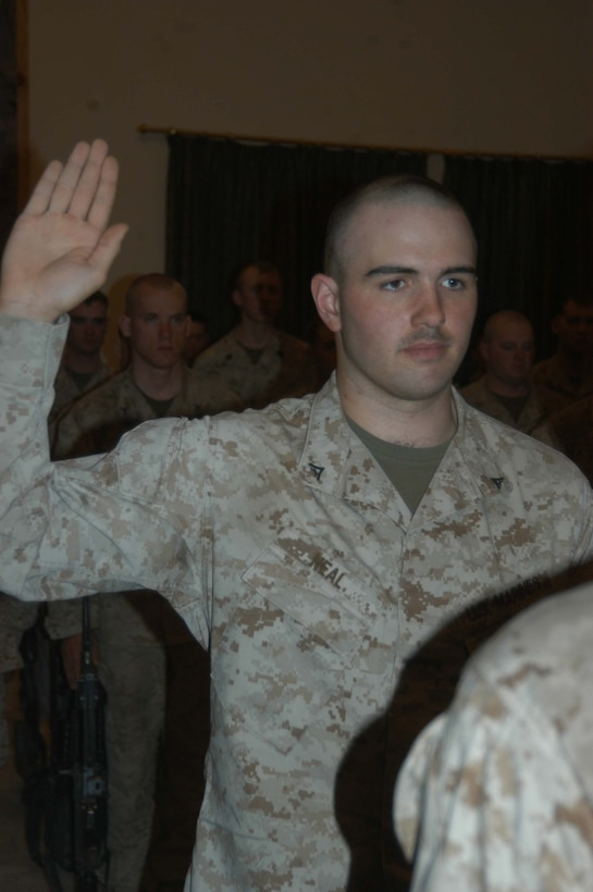 """CAMP HURRICANE POINT Ar Ramadi, Iraq (May 20, 2005) - With his right hand raised, Lance Cpl. Michael P. Neal, a machine gunner with 1st Battalion, 5th Marine Regiment's Jump Platoon, takes his oath of reenlistment during a ceremony here. The 21-year-old from Country Club Hills, Ill., swore to devote four more years of service to Corps and country. The 2001 Hillcrest High School graduate received a reenlistment bonus of $19,692, which is tax-free and will be paid in a lump sum. Oliver North and his two-man camera crew covered the event, which will later appear on the Fox News show """"Oliver in Iraq."""" Photo by: Cpl. Tom Sloan"""